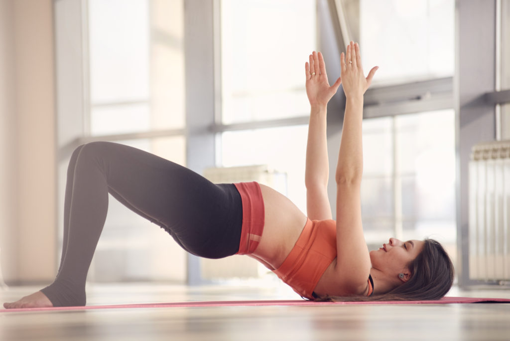 Pregnant woman doing hip thrust in yoga class Healthy Mama Brand